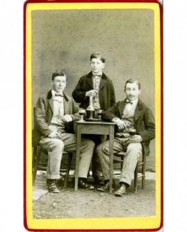 Trois jeunes hommes, verres de flacon de vin
