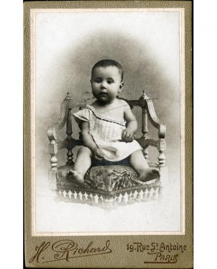 Bébé en chemise épaule dénudée assis sur une chaise