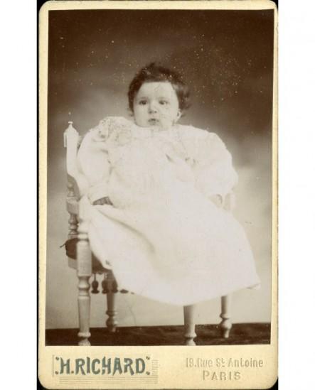Bébé assis sur une chaise (André Genty)