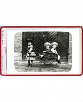 Fillette attelée à une cariole, deux garçons assis, en chapeau