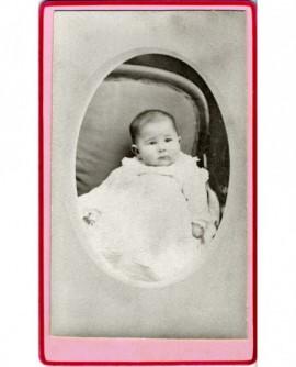 Bébé en robe assis dans un fauteuil
