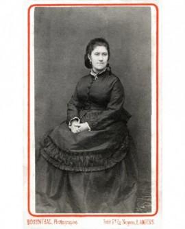 Jeune femme assise, mains jointes