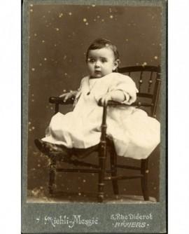 Bébé en robe longue, assis sur une chaise, chaîne et médaille au cou