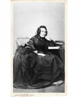 Femme en robe et mantille assise à un bureau