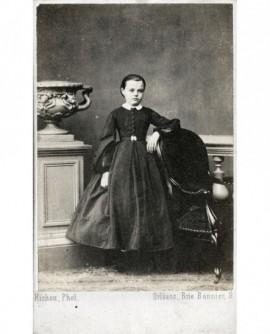 Fillette en robe à panier accoudée à une chaise. Alice Platon