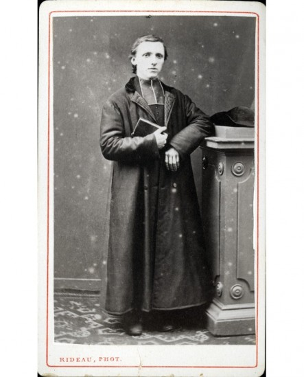 Ecclésiastique en manteau accoudé à une colonne livre à la main