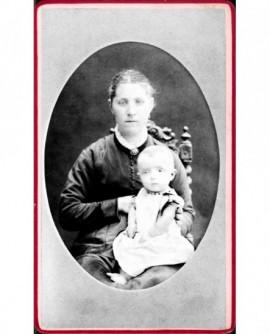 Femme en robe assise, bébé en chemise sur les genoux