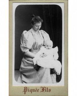Femme en robe tenant un bébé sur ses genoux