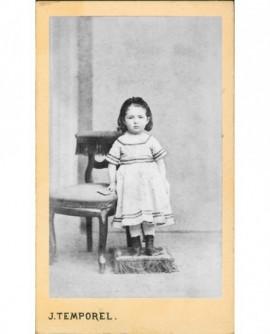 Fillette debout sur un repose-pied, appuyée sur une chaise.