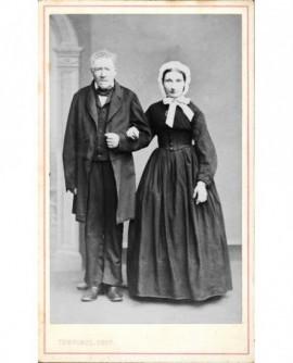 Couple debout se donnant le bras (mari plus âgé que la femme en coiffe)