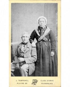 """Couple âgé: femme en coiffe debout appuyée sur l""""épaule de l'homme assis"""