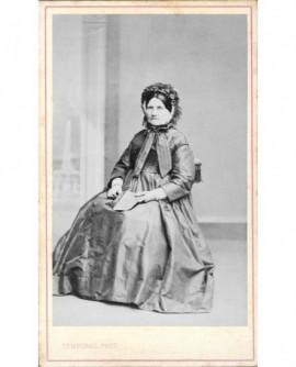 Femme âgée en bonnet assise, une brochure dans les mains