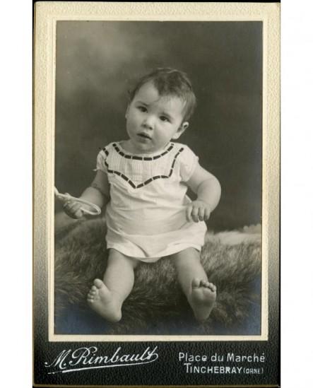 Bébé en chemise assis sur une peau de mouton hochet (jouet)