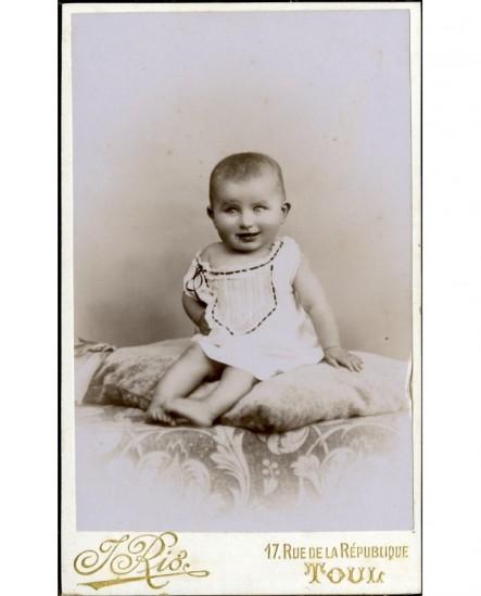 Bébé souriant en chemise, assis sur un coussin