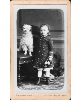 Fillette debout une fleur à la main, près d'un chien assis sur un siège.