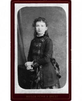 Jeune fille debout appuyée sur un meuble
