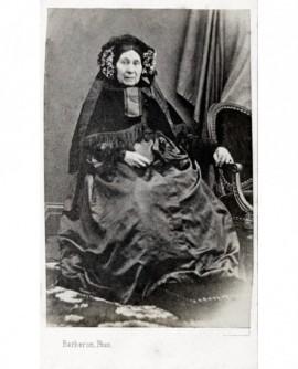 Femme en robe et capeline à fleurs assise,