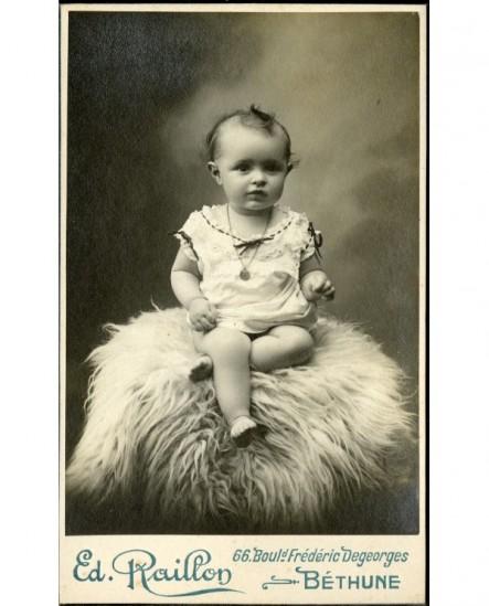 Bébé en chemise, épaule dénudée, assis sur une peau de mouton