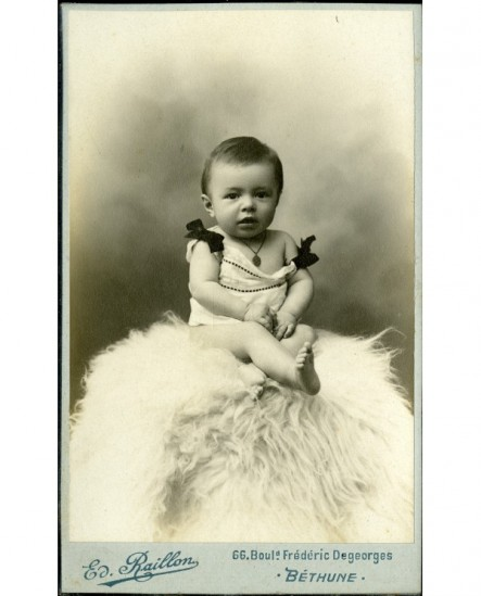 Bébé en chemise, assis sur une peau de mouton