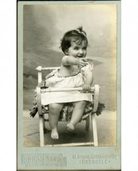 Bébé en chemise, épaule dénudée, assis sur sa chaise, tendant le bras