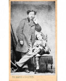 Homme à favoris et moustache debout, jeune garçon assis