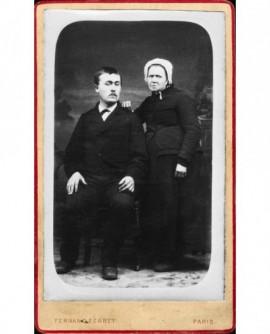 Homme moustachu assis et femme âgée debout