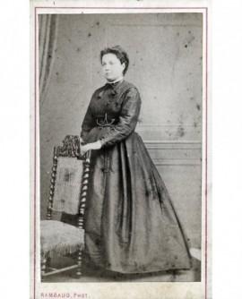 Femme en robe debout, appuyée sur une chaise