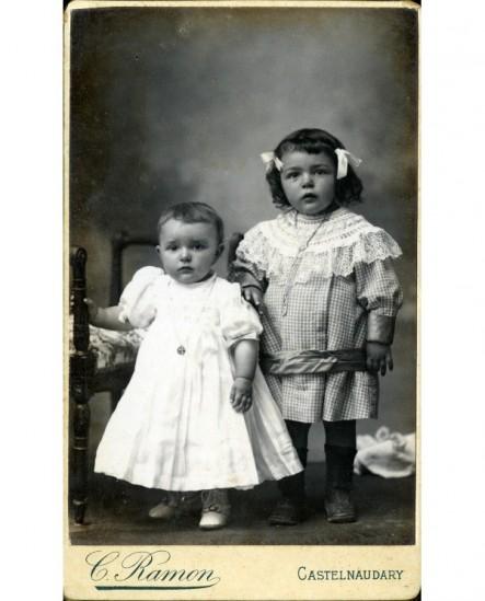 Deux enfants en robe avec médaille au cou