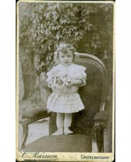 Fillette debout sur un fauteuil, bouquet dans les mains