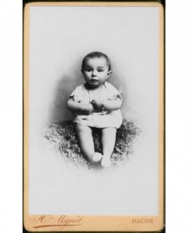 Bébé en chemise assis sur une peau de mouton