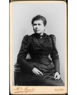 Jeune femme en robe noire assise