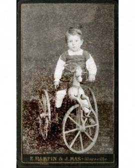 Jeune garçon en robe sur un cheval-tricycle
