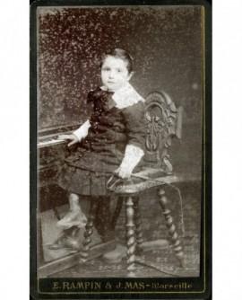 Enfant en robe assis prés d'un piano avec un fouet (jouet)