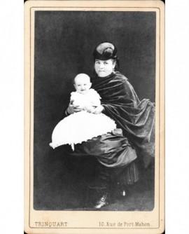 Femme en cape et toque assise, bébé sur les genoux