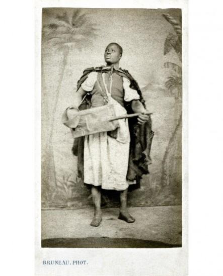 Musicien noir (joueur de cora?) debout devant une toile peinte