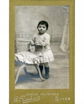 Enfant en robe appuyé sur une chaise