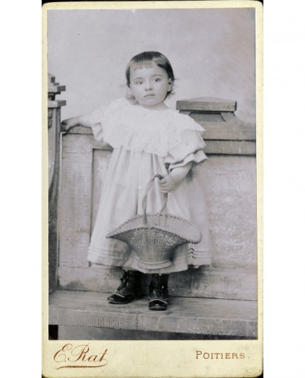 Enfant en robe tenant un panier