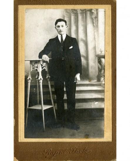 Homme en costume-cravate appuyé sur une sellette