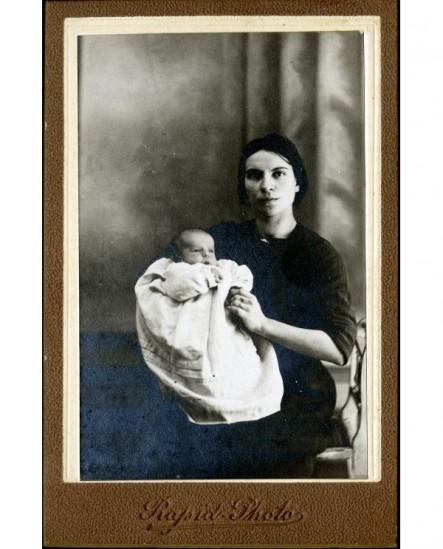 Jeune femme assise tenant un bébé