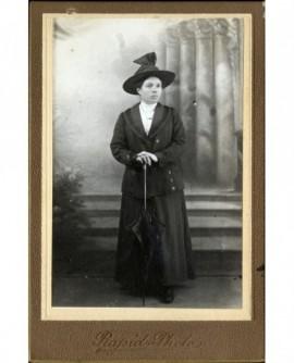 Jeune femme en chapeau debout, appuyée sur une ombrelle