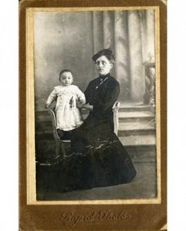 Femme en chapeau assise tenant un enfant