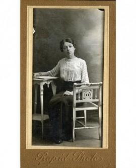 Femme en corsage assise à une table devant un livre ouvert