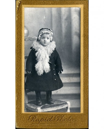 Fillette en manteau, bonnet et cache-col debout sur une chaise