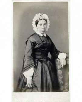 Femme en robe noire et coiffe blanche debout accoudée