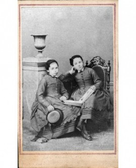 Deux fillettes en robe et bonnet, livre de photos sur les genoux