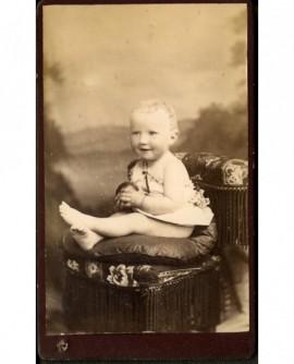 Bébé en chemise, assis sur une chaise, balle en mains (Léon Girod)