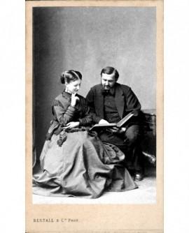 Couple assis en train de lire un livre