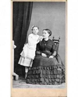 Femme assise en robe noire à volant, fillette en robe blanche