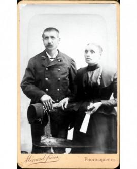 Couple debout: homme en uniforme de postier, femme tenant un éventail