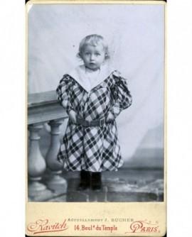Enfant en robe à carreaux accoudé à une balustrade